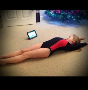 This gymnast is lying down in front of her Ipad performing gymnastics