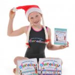 This is an image of a girl showing our books Dvd's and a leotard from Christmas Gymnastics Gifts range